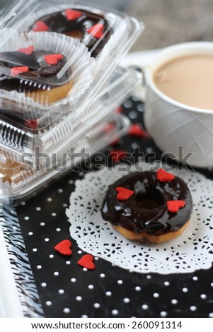 Doughnut with chocolate glazing and tea cream and in packaging