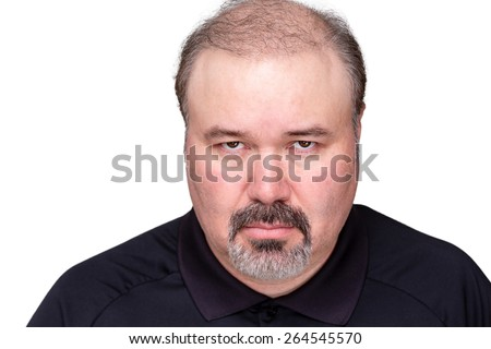Dour angry middle-aged man glowering at the camera from under his brows, head and shoulders isolated on white - stock photo