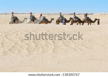 DOUZ, KEBILI, TUNISIA - SEPTEMBER 17: Beduins leading tourists on camels at short tourist tour around the beginning so called Doors of Sahara desert on September 17,2012 in Douz, Tunisia.