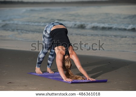 Down Dog Yoga pose in pattern tights along coastline.