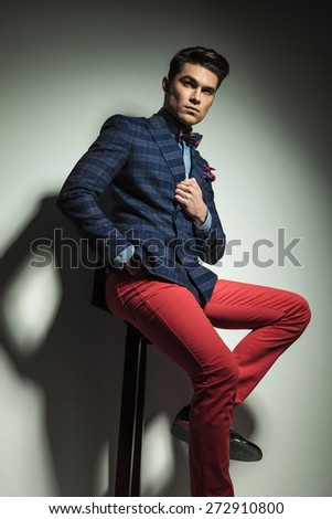 Down view of a handsome fashion man holding one hand in his pocket while siting on a stool. - stock photo