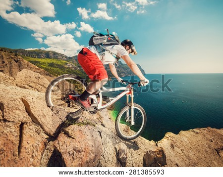 Downhill bike. Down from the mountain on a mountain bicycle on a rocky trail. Extreme sport. Man riding outdoors lifestyle.