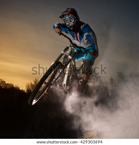Downhill cycling. Man jump on a mountain bike with dust. Extreme sport. - stock photo