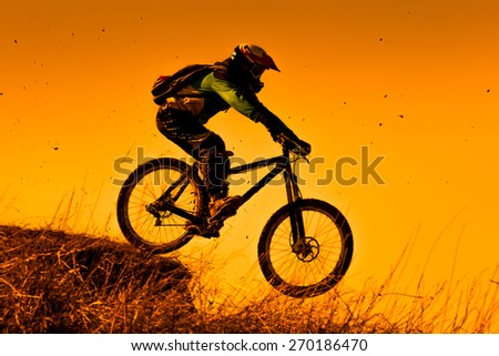 Downhill mountain bike ride at sunset - stock photo