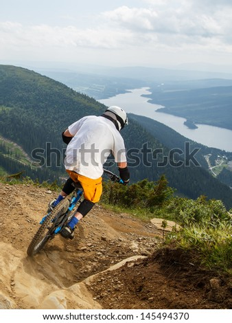 Downhill mountain biker making a turn on rocky trail in Are, Sweden.