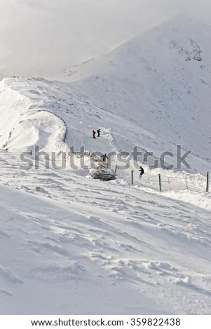 Downhill Skiers and snowboarder on Kasprowy Wierch in Zakopane in winter. Zakopane is a town in Tatra Mountains. Kasprowy Wierch is a mountain in Zakopane and the most popular ski area in Poland - stock photo
