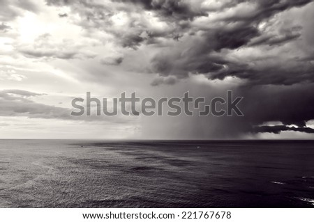 downpour over sea with stormy clouds - stock photo