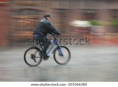 Downpour. Wet cyclist rides through the streets on a rainy day . Intentional motion blur - stock photo