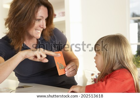 Downs Syndrome girl having speech therapy - stock photo