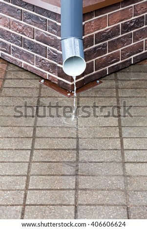downspout against brick wall during a heavy rain - stock photo