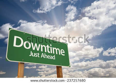 Downtime Just Ahead Green Road Sign with Dramatic Clouds and Sky. - stock photo