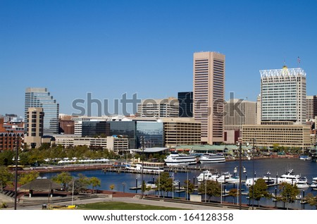 Downtown Baltimore, Maryland city inner harbor skyline showing the marina, buildings and business on a clear sunny day.