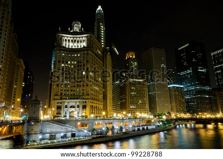 Downtown Chicago by night from river bank - stock photo