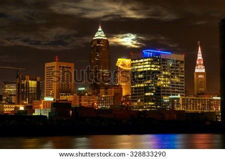 Downtown Cleveland, Ohio, from the west bank of the Cuyahoga with the full moon rising behind the clouds - stock photo
