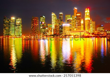 Downtown Core of Singapore reflecting in the river at night - stock photo