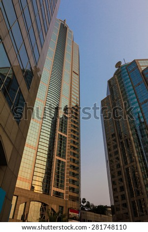 Downtown corporate business district architecture: glass reflective office buildings against blue sky - stock photo