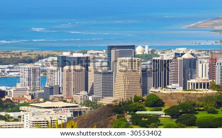 Downtown Honolulu skyscrapers from a high overlook with part of the Punchbowl National Cemetery in foreground - stock photo