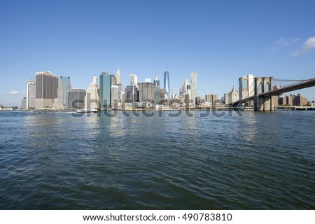 Downtown Manhattan skyline view from Brooklyn of the Brooklyn Bridge with East River in New York City