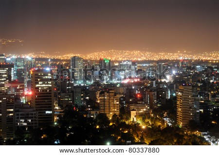 Downtown Mexico City skyline at night, with brightly lit suburban barrios in the background - stock photo