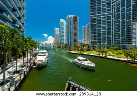 Downtown Miami along the Miami River inlet with Brickell Key in the background and yacht cruising by. - stock photo