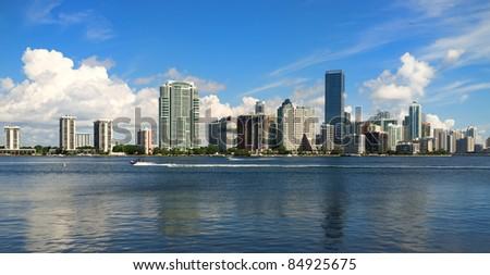Downtown Miami skyline along Brickell Avenue with skiers enjoying Biscayne Bay. - stock photo