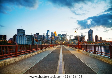 Downtown Minneapolis, Minnesota at night time as seen from the famous stone arch bridge - stock photo