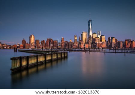 Downtown New York observed from Jersey City, across the Hudson River. The Financial District skyscrapers have an orange glow from the last rays of the sunset. - stock photo