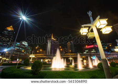 Downtown of Bangkok from an entrance of Lumphini park by road Rama IV and a skytrain railway at night , skyscrapers and canon logo , January 16  2017
