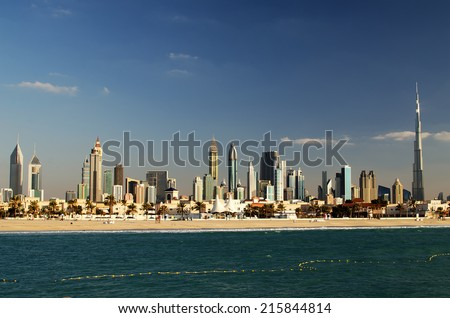 Downtown of Dubai (UAE) in the evening. Burj Khalifa, the tallest building in the world. Beautiful skyline of modern skyscrapers of  city built in the desert.  The view from the beach of Persian Gulf.