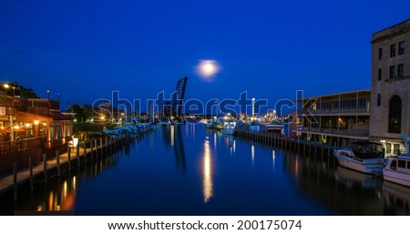 Downtown Port Huron, Michigan in the moonlight, with a silhouette of a historical railroad drawbridge in the background. - stock photo