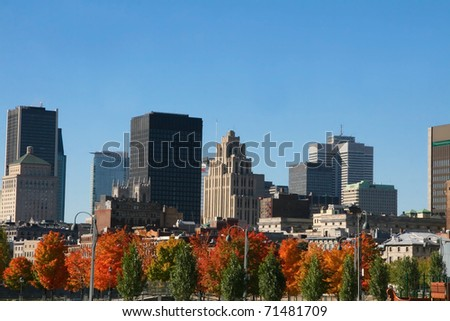 Downtown skyline with trees showing thier autumn colors - stock photo