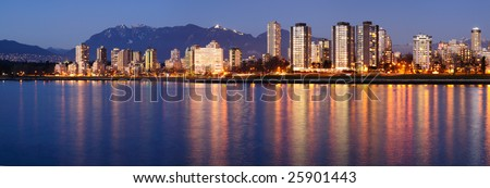 Downtown Vancouver on a winter evening glows in the dusk against a backdrop of majestic mountains