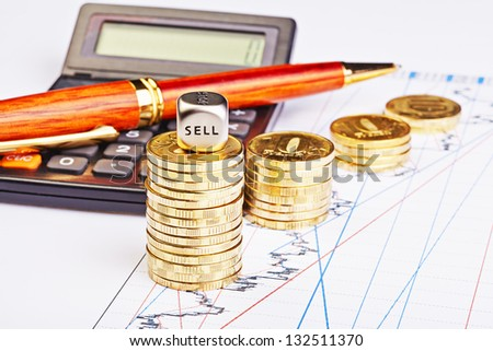 Downtrend coins stacks, calculator, pen and dices cube with the word SELL on financial chart. Selective focus - stock photo