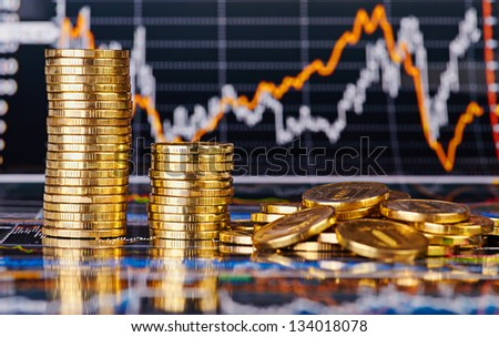 Downtrend stacks of golden coins and  financial stock charts as background. Selective focus - stock photo