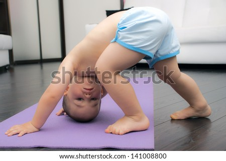 Downward facing dog pose by baby boy two years old - stock photo