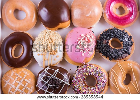 Dozen of vibrant artisan donuts from above in office brunch box - stock photo