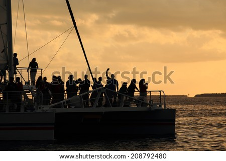 Dozens of silhouetted passengers, one waving a greeting, enjoy a sunset sail on a large catamaran. - stock photo