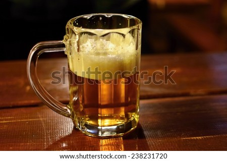 Draft beer by the glass. Honest Czech lager on an old wooden table. - stock photo