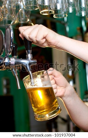 Draft beer pour in a glass from the crane - stock photo
