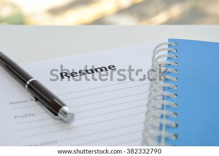 Draft of Resume with pen and notebook - stock photo
