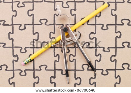 Drafting Compass with Pencil on Finished Puzzle - stock photo
