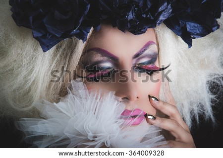 Drag queen with spectacular makeup, glamorous trashy look, posing happily and charming camera from sideways angle