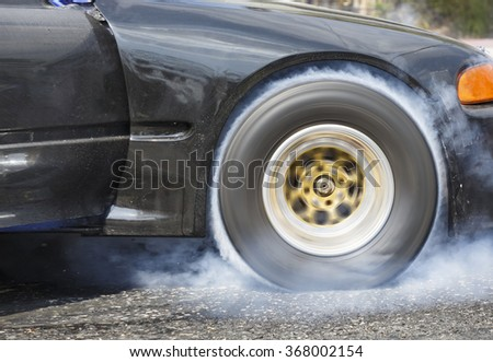 Drag racing car burns rubber off its tires in preparation for th - stock photo