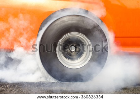 Drag racing car burns rubber off its tires in preparation for the race - stock photo