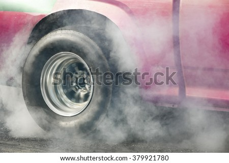 Drag racing car burns rubber off its tires in preparation for the race.