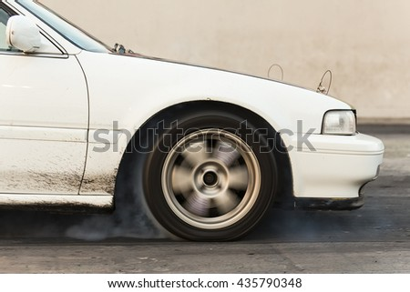 Drag racing car from side tire burnout in preparation for the race. (Motion blur) - stock photo
