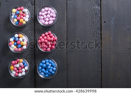 dragees, sugar coated pills at glass dish, on black wood table background - stock photo