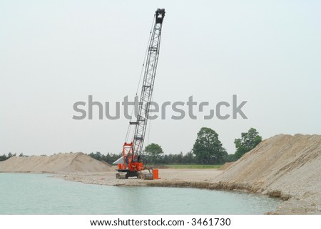 dragline used to pull gravel out of underwater quarry - stock photo