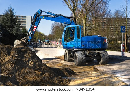 Draglines at work to renew the pavement of a road in the city. Blue excavators and bright blue sky in early spring. Horizontal image. - stock photo