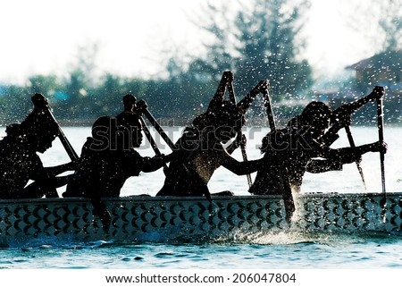 Dragon boat participant silhouetted by backlit. - stock photo